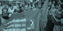 Kvinnor på en demonstration för högre minimilön i Sri Lanka. En kvinna håller upp en banderoll med IndustriALL:s logga på och tittar in i kameran.