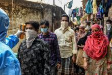Läkare kollar temperaturen hos invånare i Mumbai.